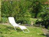 Die Aufnahme zeigt einen Liegestuhl in einem Garten