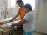 Die Aufnahme zeigt zwei Personen in einer Werkstatt.