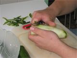 Die Aufnahme zeigt eine Person beim Schälen einer Gurke.