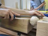 Die  Aufnahme zeigt eine Person bei der Bearbeitung einer Holzkugel.
